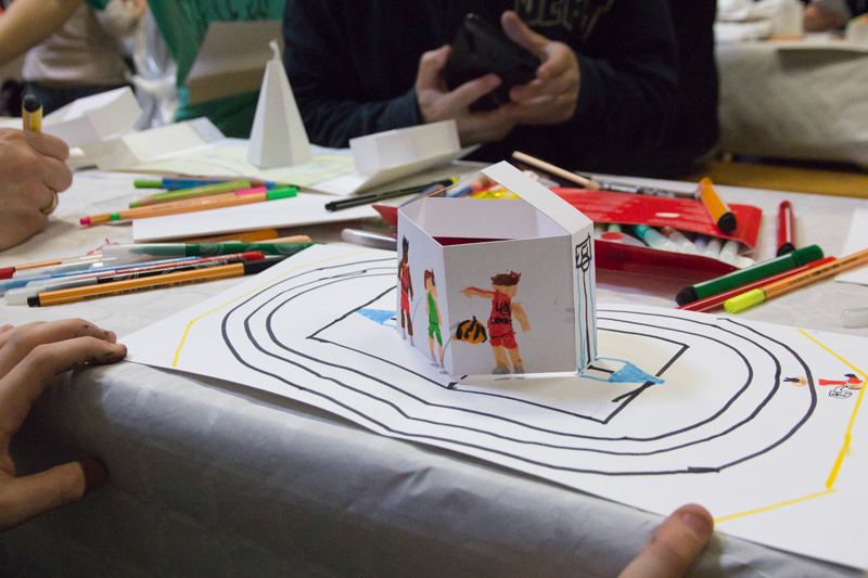 Un jeune participant a dessiné des sportifs et une piste de course autour du pop-up en papier.