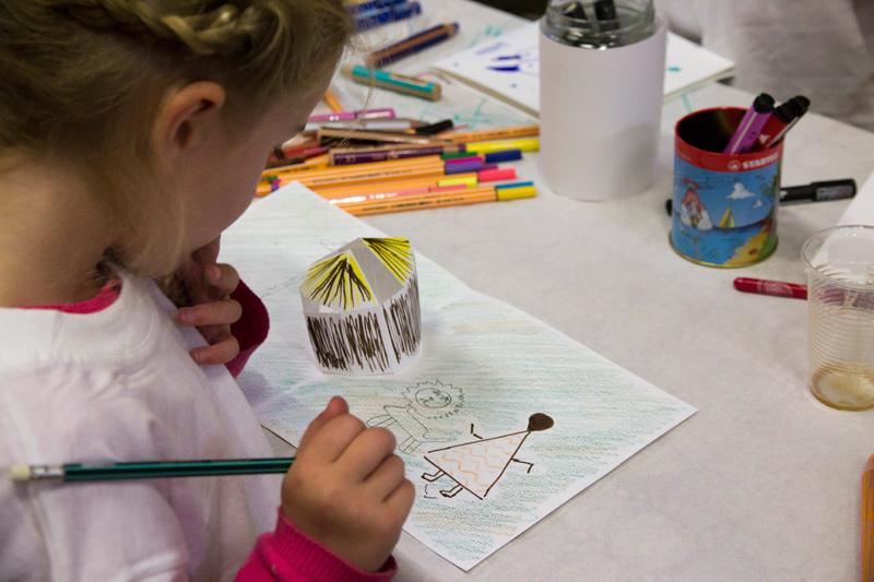 Une jeune participante réfléchi au dessus de son dessin et de son bâtiment colorié.