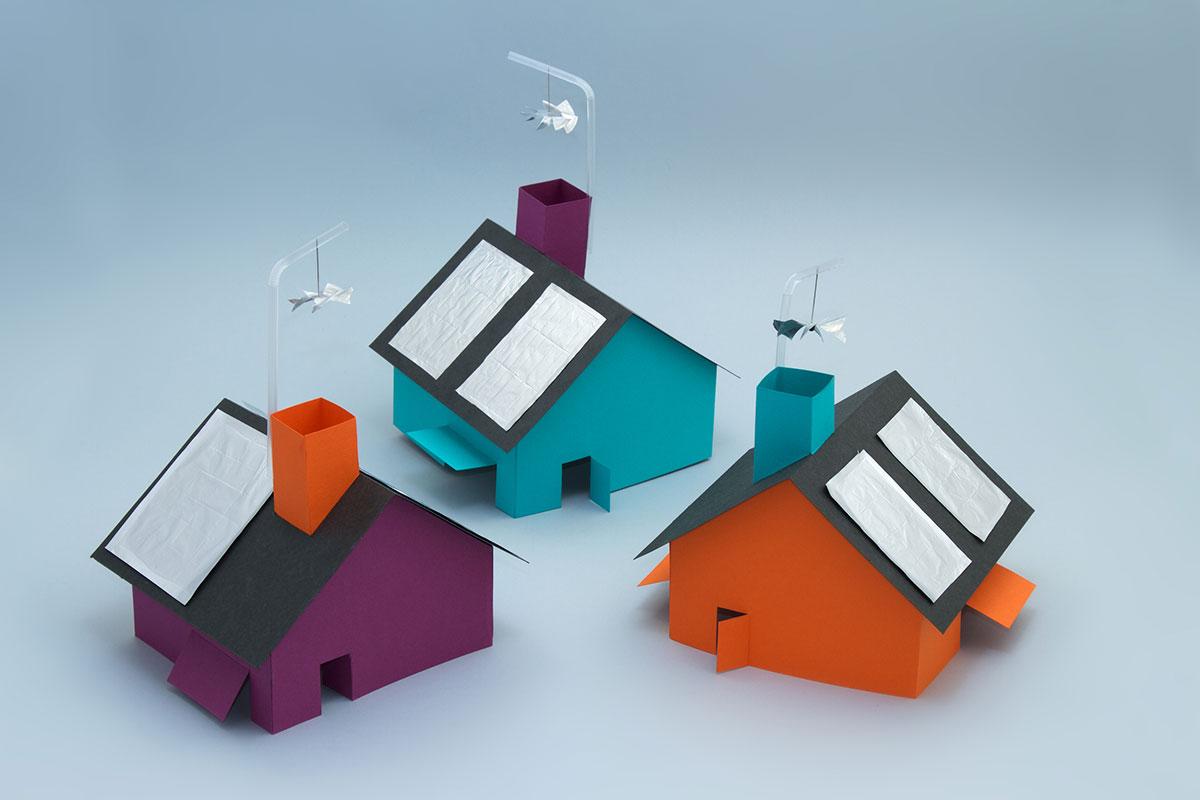 Trois maisons en papier coloré sont décorées de panneaux solaires en aluminium. Des hélices sont placées au dessus des cheminées. Elles tournent lorsque la maison est placée au soleil.