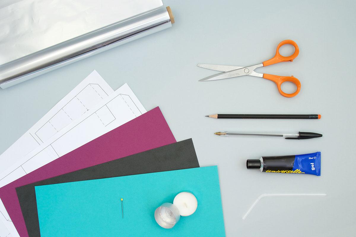 Le matériel de l'activité est montré sur le plan de travail : papier, bougie, ciseaux, colle...