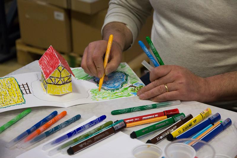Un participant adulte est en train de colorier au feutre le pop-up en blanc, en maison alsacienne.