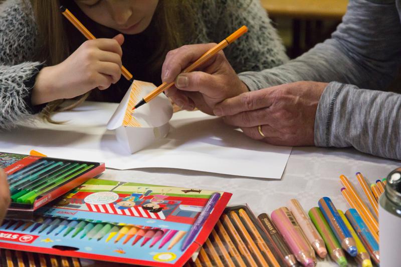 Une fille et son grand-père personnalisent la même maison en papier.
