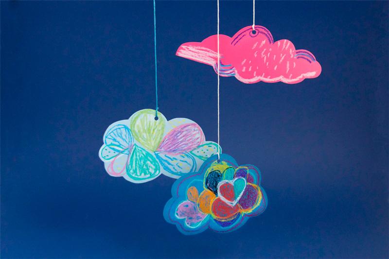 Suspension de trois nuages décorés au STABILO woody 3in1, photographiés sur fond bleu.